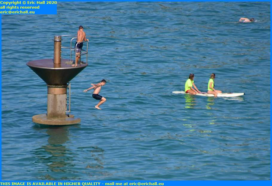 lifeguards on paddleboard kids jumping off diving platfrom plat gousset granville manche normandy france eric hall