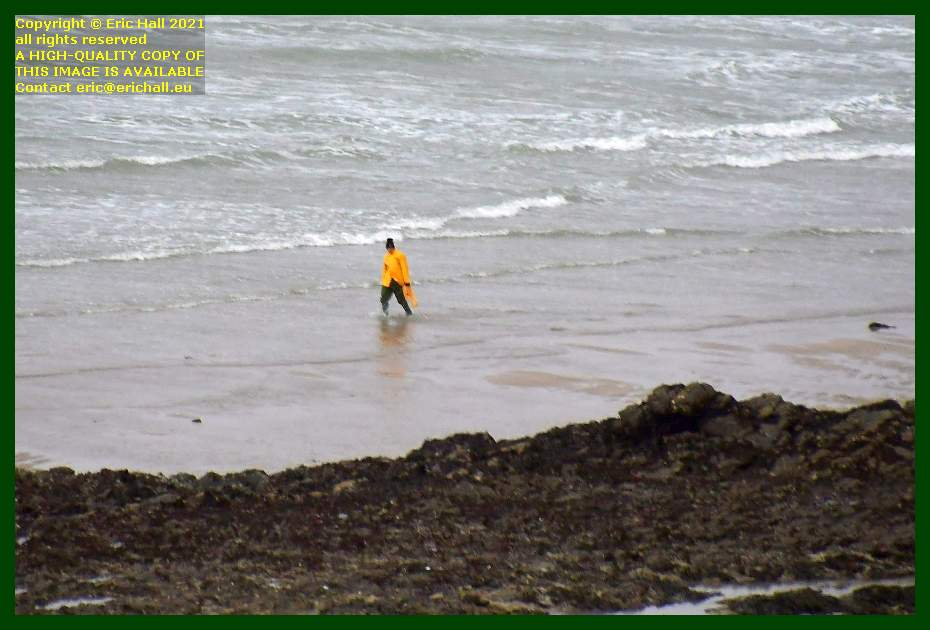man wading in water in waterproofs beach place d'armes Granville Manche Normandy France Eric Hall
