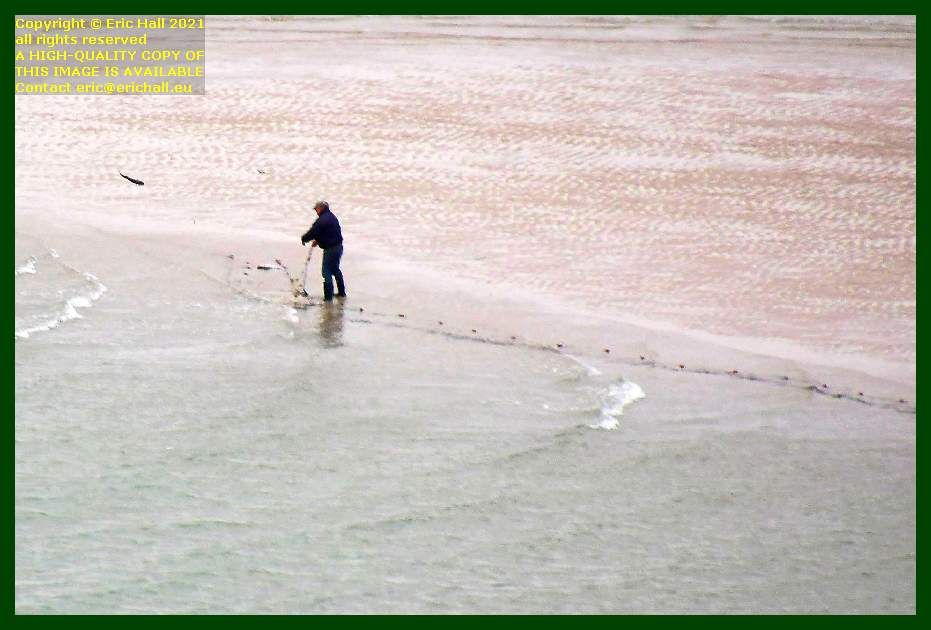 fisherman throwing fish back into sea beach rue du nord Granville Manche Normandy France Eric Hall
