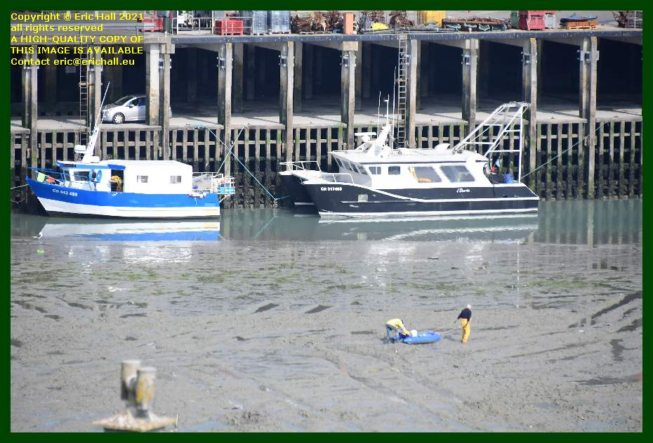 men dragging boat across mud fishing boats grounded out port de Granville harbour Manche Normandy France Eric Hall