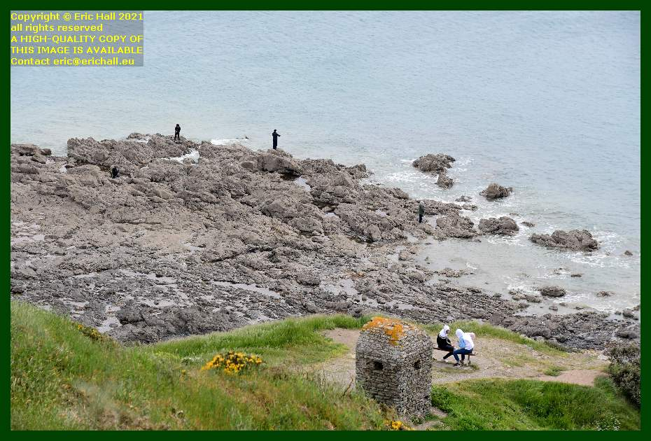 people fishing on rocks seated on bench pointe du roc Granville Manche Normandy France Eric Hall