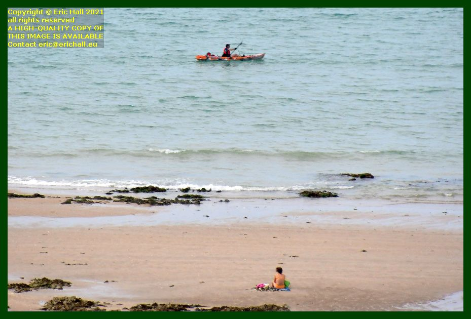man in canoe woman sunbathing on beach place d'armes Granville Manche Normandy France Eric Hall