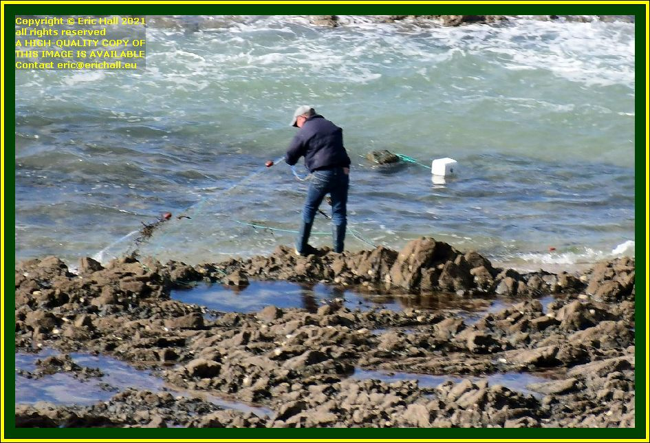 man fishing with net place d'armes Granville Manche Normandy France Eric Hall photo September 2021